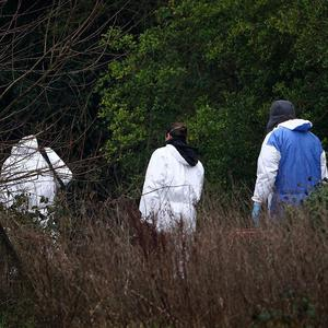 Police forensic officers enter the scene around Reed Pond in Canterbury, Kent, following the discovery of two bodies