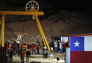 Mining Minister Laurence Golborne and rescue chief Andre Sougarrete, right, hold hands as rescue worker Manuel Gonzalez Paves is lowered in the capsule into the mine where miners are trapped to begin the rescue  at the San Jose Mine near Copiapo, Chile.(AP Photo/Roberto Candia)