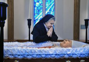 A nun prays at the open casket of Cardinal Cahal Daly at St Peter's Cathedral in west Belfast