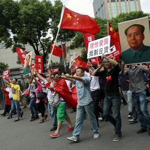 Protesters carrying Chinese flags and signs with anti-Japan messages march in front of the Japanese Consulate General in Shanghai (AP)