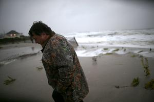 CAPE MAY, NJ - OCTOBER 29:  Andy Becica walks off the beach as heavy surf from from Hurricane Sandy washes in, on October 29, 2012 in Cape May, New Jersey. Later today the full force of Hurricane Sandy is expected to hit the New Jersey coastline bringing heavy winds and floodwaters.  (Photo by Mark Wilson/Getty Images)