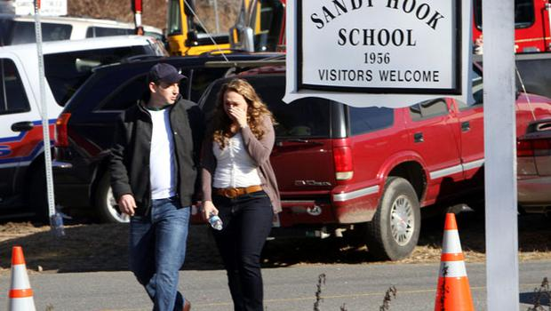 Parents walk away from the Sandy Hook Elementary School with their children following a shooting at the school, Friday, Dec. 14, 2012 in Newtown, Conn. A man opened fire inside the Connecticut elementary school where his mother worked Friday, killing 26 people, including 18 children, and forcing students to cower in classrooms and then flee with the help of teachers and police. (AP Photo/The Journal News, Frank Becerra Jr.) MANDATORY CREDIT, NYC OUT, NO SALES, TV OUT, NEWSDAY OUT; MAGS OUT