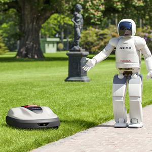 Honda's Asimo walking talking robot with the company's new robot lawnmower (AP)