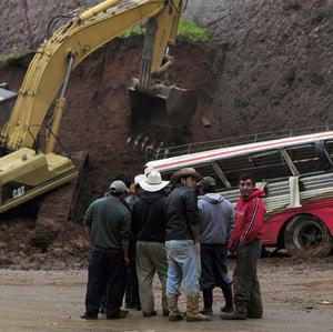 The first mudslide partially buried a bus on a road leading north of the capital toward Mexico