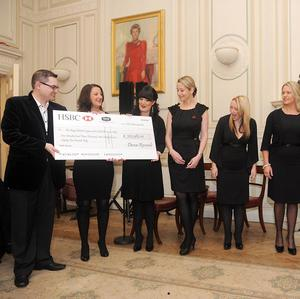 Composer Paul Mealo joins the Military Wives Choir to present a cheque to the Royal British Legion and SSAFA Forces Help