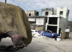 The hand from the body of an earthquake victim hangs from a pick-up truck loaded with bodies waiting to be unloaded at a cemetery in Port-au-Prince,Thursday, Jan. 14, 2010
