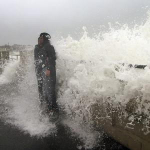 A couple posing for a picture get hit by a wave in Hampton, New Hampshire (AP)