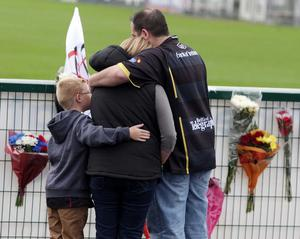A family console each other while reading messages of condolence at the home of Ulster Rugby