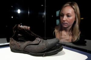 A woman examines a leather boot in an exhibition of artefacts recovered from the wreck of the Titanic on November 3, 2010 in London, England