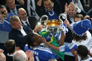 MUNICH, GERMANY - MAY 19: Didier Drogba (C) and club owner Roman Abramovic (L) celebrate with the trophy after their victory in the UEFA Champions League Final between FC Bayern Muenchen and Chelsea at the Fussball Arena München on May 19, 2012 in Munich, Germany.  (Photo by Christof Koepsel/Bongarts/Getty Images)