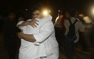 Employees of the Taj Hotel comfort each other after they were rescued from the hotel in Mumbai, India, Thursday, Nov. 27, 2008. Teams of heavily armed gunmen have stormed luxury hotels and other sites in coordinated attacks across India's financial capital, killing at least 82 people and taking Westerners hostage. (AP Photo/Gautam Singh)