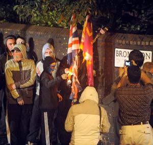 Masked youths set fire to a Union flag and a loyalist UVF flag at Brompton Park in Ardoyne on a fourth consecutive night of rioting July 2010