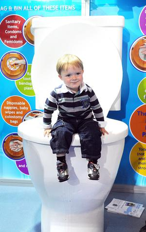 2 year old Sam Geary finds himself a huge toilet to sit on at the NI Water stand