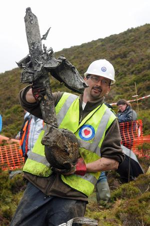 John McNee holds the rear wheel of the Spitfire which has been unearthed from bogland outside Gleneely, County Donegal. Picture Martin McKeown. Inpresspics.com. 28.6.11