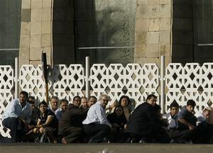 People take cover at the sound of gunfire outside The Taj Hotel in  Mumbai, India, Thursday, Nov. 27, 2008. Black-clad Indian commandoes raided two luxury hotels to try to free hostages Thursday, and explosions and gunshots shook India's financial capital a day after suspected Muslim militants killed people. (AP Photo/Rajanish Kakade)