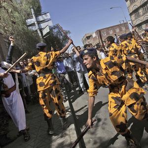 Yemeni riot police charge towards anti-government demonstrators in Sanaa (AP)