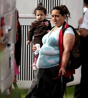 A Romanian woman and her child make their way to the bus yesterday