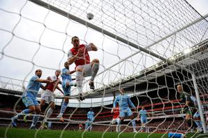 LONDON, ENGLAND - APRIL 08:   Robin van Persie of Arsenal's shot at goal hits Thomas Vermaelen of Arsenal in the face and goes over the bar during the Barclays Premier League match between Arsenal and Manchester City at Emirates Stadium on April 8, 2012 in London, England.  (Photo by Michael Regan/Getty Images)