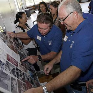 Andres Garcia, left, and Jose Reyes, former Pedro Pan children, look at old pictures at Camp Matecumbe (AP)