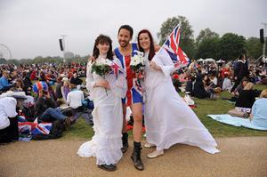 LONDON, ENGLAND - APRIL 29:  Two girls dressed as brides with a guy wearing a Union Jack Skirt pose for the camera in Hyde Park as they wait to watch the Royal Wedding of Prince William to Catherine Middleton at Westminster Abbey on April 29, 2011 in London, England. The marriage of the second in line to the British throne is to be led by the Archbishop of Canterbury and will be attended by 1900 guests, including foreign Royal family members and heads of state. Thousands of well-wishers from around the world have also flocked to London to witness the spectacle and pageantry of the Royal Wedding.  (Photo by Christopher Lee/Getty Images)