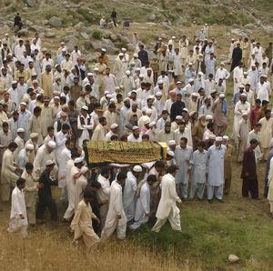 Villagers carry a dead body of a suicide bombing victim for burial (AP)
