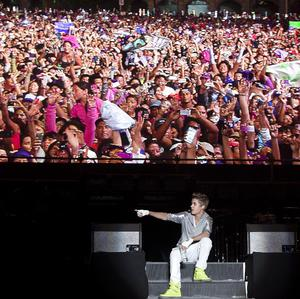 Sitting under a video screen displaying people attending his show, pop star Justin Bieber performs during a free open-air concert in Mexico City (AP)