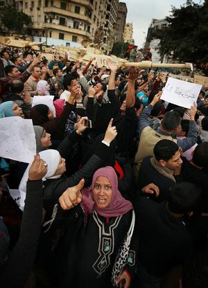 CAIRO, EGYPT - JANUARY 30:  A woman shouts as she blocks the entry of army tanks to Tahrir Square on January 30, 2011 in Cairo, Egypt. Cairo remained in a state of flux and marchers continued to protest in the streets and defy curfew, demanding the resignation of Egyptian president Hosni Mubarek. As President Mubarak struggles to regain control after five days of protests he has appointed Omar Suleiman as vice-president. The present death toll stands at 100 and up to 2,000 people are thought to have been injured during the clashes which started last Tuesday. Overnight it was reported that thousands of inmates from the Wadi Naturn prison had escaped and that Egyptians were forming vigilante groups in order to protect their homes.   (Photo by Peter Macdiarmid/Getty Images) *** BESTPIX ***