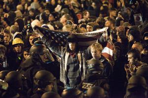 PORTLAND, OR - NOVEMBER 13: A man holds up an American flag as defiant protestors refuse to leave Occupy Portland November 13, 2011 in Portland, Oregon.  In spite of an eviction notice for early Sunday morning, Portland police delayed closing two downtown parks early today as thousands of people converged to support the Occupy Portland movement.(Photo by Natalie Behring/Getty Images)