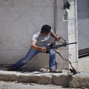 A Free Syrian Army fighter fires his weapon during clashes with Syrian troops near Idlib (AP)