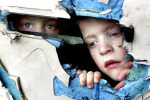 December 2002 Six year old twins Sean and Dean Fegan peer through the hole where their letterbox had been following an explosion which rocked their home early this morning in an attack claimed this afternoon by the loyalist Red Hand Defenders who had put a pipe bomb through their letterbox. The blast happened in a Catholic area of Oldpark Road in north Belfast. Picture by Justin Kernoghan