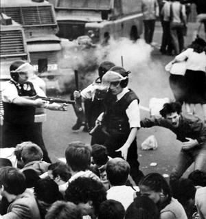 August 1984 John 'Sean' Downes clutches his chest as he is fatally wounded by a plastic bullet.   The incident occured after police moved in to try to arrest Noraid fund raiser Martin Galvin who was the subject of a UK exclusion order and who had just been paraded by Sinn Fein on a platform outside Connolly House in Andersonstown. Picture By Alan Lewis
