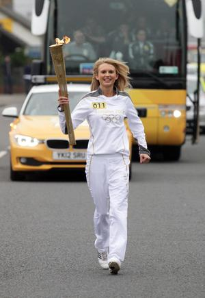 Jessica Craig carrying the Olympic Flame on the Torch Relay leg between Newcastle and Downpatrick