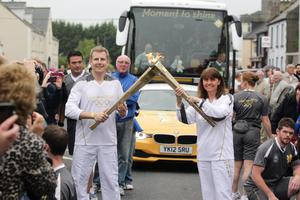 Patrick Kielty passing the Olympic Flame to torchbearer 015 Deirdre Brennan on the Torch Relay leg between Newcastle and Downpatrick
