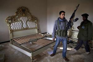 A Libyan rebel stands in the damaged and vandalized former bedroom that was used by Libyan leader Moammar Gadhafi and his family at the terminal of the airport in Benghazi, in eastern Libya, Monday, Feb. 28, 2011. (AP Photo/Kevin Frayer)