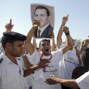 A pro-Mubarak supporter holds a photo of the former president during a demonstration outside the court where he is on trial (AP)