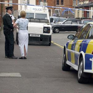 Two women were pulled out of a parked car in west Belfast by masked men