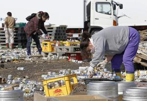 People put away cans containing beer and juice swept out from a beer factory in Sendai, Miyagi Prefecture, northern Japan, Sunday, March 13, 2011, two days after a powerful earthquake and tsunami hit the country's east coast. (AP Photo/Kyodo News) JAPAN OUT, MANDATORY CREDIT, NO SALES IN CHINA, HONG  KONG, JAPAN, SOUTH KOREA AND FRANCE