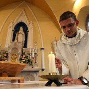 Father Stanislaw Adamiak lights a candle at the Catholic church in the parish of St Martin in Jersey