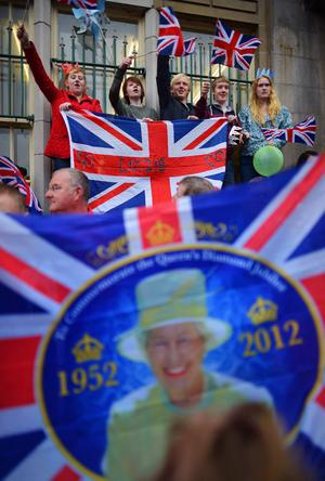 ENNISKILLEN, NORTHERN IRELAND - JUNE 26:  People wave Union Jack flags as Queen Elizabeth II and Prince Philip, Duke of Edinburgh arrive to visit Macartin's Cathedral on June 26, 2012 in Enniskillen, Northern Ireland. The Queen and Duke of Edinburgh, on a Diamond Jubilee visit to Northern Ireland, are due to meet with former IRA leader and NI's Deputy First Minister Martin McGuinness.  (Photo by Jeff J Mitchell/Getty Images)