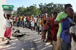 People stand in line to get food being distributed by United Nations peacekeepers on January 22, 2010 in Port-au-Prince, Haiti. International aide continues to slowly arrive in the earthquake ravaged city