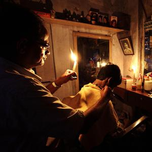 An Indian barber works while holding a candle (AP)