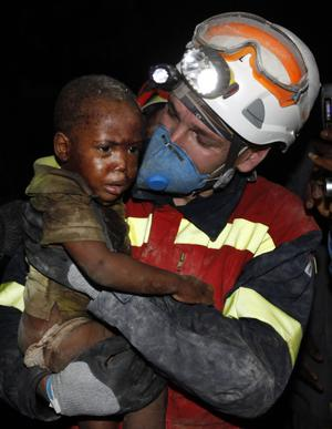 A Spanish rescuer carries two-year-old Redjeson Hausteen