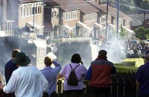 Smoke spreads as a pipe bomb explodes after it was thrown at police and army lines by protesting loyalists this morning in the Glenbryn area of Ardoyne, North Belfast, after Holy Cross Primary school children were marched through lines of Police and army on the second day back to school.