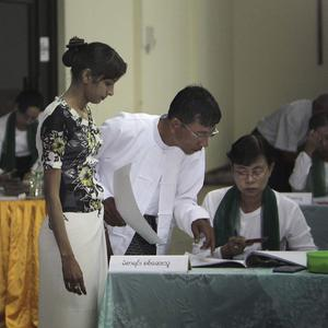 A Burmese voter waits to cast her ballot as election officials search a list of names at a polling centre in Yangon. (AP)