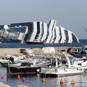 The luxury cruise ship Costa Concordia leans on its starboard side as seen from the Giglio harbour (AP)