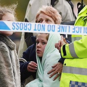 People wait behind a police cordon as emergency services attend the scene of a gas explosion in Salford
