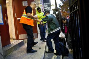 NEW YORK, NY - OCTOBER 28:  A man is helped up the stairs at Seward Park High School, which is doubling as an  evacuation center for Hurricane Sandy, on October 28, 2012 in New York City. Sandy, which has already claimed over 50 lives in the Caribbean, is predicted to bring heavy winds and floodwaters as the mid-atlantic region prepares for the damage.  (Photo by Andrew Burton/Getty Images)