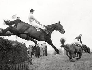 File photo dated 24//03/56 of Dick Francis, the champion jockey turned best-selling thriller writer, who has died at the age of 89, jumping the Queen's Mother's Devon Loch, over the feared Becher's Brook during the Grand National Handicap Steeplechase at Aintree