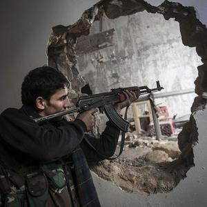 A Free Syrian Army fighter aims his weapon at government forces during clashes in Aleppo (AP)