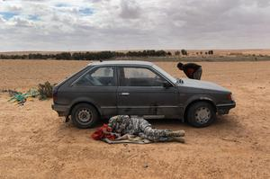 RAS LANUF, LIBYA - MARCH 09:  A rebel fighter naps ahead of a battle against government troops near the frontline on March 9, 2011 near Ras Lanuf, Libya. The rebels pushed back government forces loyal to Libyan leader Muammar Gaddafi towards Ben Jawat.  (Photo by John Moore/Getty Images)